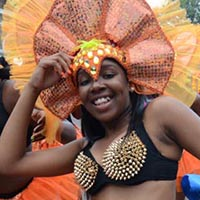 A woman wearing a black bra with golden spikes on it and a orange skirt and headdress.