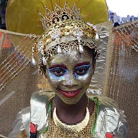 Girl wearing a golden outfit, golden face-paint, with blue and red details around the eyes, and a golden crown.
