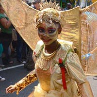Girl wearing a golden dress with her face painted in gold, blue and red, wearing a crown above her head and a big half moon similar golden construction on her back.