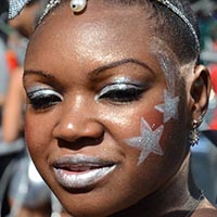 Close-up of a woman with silver make-up, silver lips, silver stars painted on her face and a silver crown-headdress.