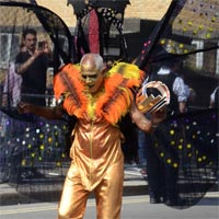 Nolan wearing golden costume with long orange and yellow feathers on his shoulders and big swan shaped backpack in black carring his golden headdress on his left hand.