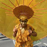 Member of Elimu dressed in a golden and yellow outfit with a headdress in the same colour. The headdress is circular and has got bars on the edge leading to a huge golden disc.