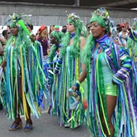 Members of Elimu performing on the street in green, blue and yellow ribbons-dresses.