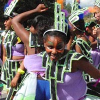 Members of Elimu, meanly young women, wearing a purple top and lace-skirt with a design out of black squades outlined with green colour, over the shirt, the skirt and the hair.