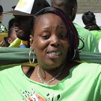 "Woman wearing a green elimu carnival shirt with the logo ""Apocalypso"" on it."