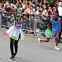 Three youngsters dressed in colourful costumes, such as lace-skirts, performing together with colourful ribbons.