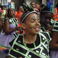 Members of Elimu performing on the street in purple and green lace skirts, purple tops and a design out of black squades with green sparkling edges above them.
