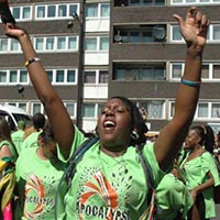 "Woman dressed in green Elimu shirt with the label ""Apocalypso"" cheering"