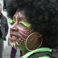 Close-up of a woman with pink and green face-paint and neon green eyelashes