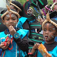 Youngsters of Elimu, dressed in blue and with paint on their face, having a little break and eating some sweets before they perform.