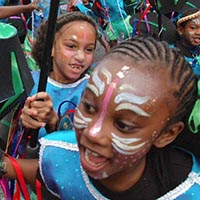 Youngsters of Elimu, dressed in blue, with paint on their face and headdress, running into the street as into a battle, as a part of their performance.