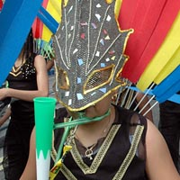 Photo of child in black costume and black mask in Elimu Mas Band at Notting Hill Carnival