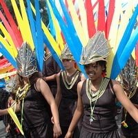Photo of young people in black costumes and black masks in Elimu Mas Band at Notting Hill Carnival