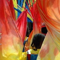 The red and yellow costume flags of Elimu Mas Band filling the street at Notting Hill Carnival