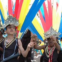 Photo of young people dancing in black costumes and black masks in Elimu Mas Band at Notting Hill Carnival