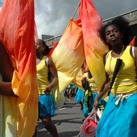 Girls in a costume of yellow top and blue shorts carrying red and yellow flags of Elimu Mas Band filling the street at Notting Hill Carnival