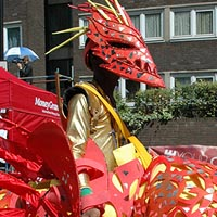 Man wearing gold top, a large red mask and large costume in the parade of Elimu Mas Band at Notting Hill Carnival