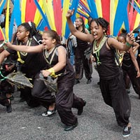 Young people in black costumes and black masks, running with arms outstretched, in Elimu Mas Band at Notting Hill Carnival