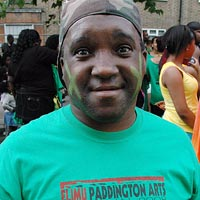 Man in green T-shirt that has Paddington Arts 'Canboulay' design of women in balck and red
