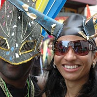 Man wearing an ornate black mask and a girl in dark glasses wearing a headdress with horns