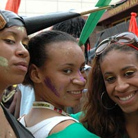 Three girls pose for the camera, one in a black costume with horns, one in green and one with dark glasses.