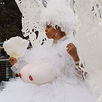 Woman in large white dress with hooped skirt and a backpack supporting huge white decorated wings. She is the Queen of Elimu Mas Band at Notting Hill Carnival