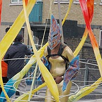 Person wearing a gold costume and mask, with a backpack that supports a framework around and above them which supports an arrangement of red, yellow and blue streamers that completely surround them