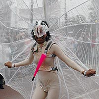 A girl wearing a pale costume with a backpack that supports a circular wing of white gossamer