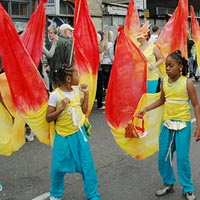 Young girls in a costume of yellow top and blue shorts carrying red and yellow flags of Elimu Mas Band filling the street at Notting Hill Carnival