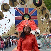 "Woman wearing a orange dress with a skirt out of three big horizontal discs, a headdress out of feathers and a transparent banner with the letters ""Lovers Rock"" on it."