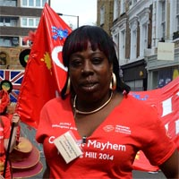 Sophie wearing red T-shirt and black short skirt carring a flag at Notting Hill Carnival