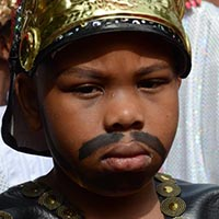 Close-up of a boy dressed up as a Roman, with a golden helmet with red feathers, a black beard painted on his face and a roman black uniform with golden buttons.