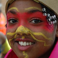 Close-up of a girl with yellow and red colour painted on her face and pearls in her hair.
