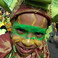 Child with its face painted in green and yellow for a dragon costume.