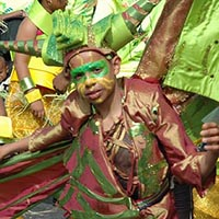Child in a dragon costume, with wings, green on the outside and brown on the inside, and a dragon-hat on its head.