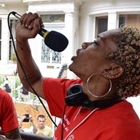 Two members of Elimu, wearing red shirts, the man got headphones on, the woman sings in a microphone.