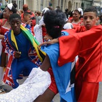 Boys from the carnival group Elimu in colourful costumes, performing with some girls in sparkling red outifts with white laces beneath.