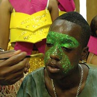 Painting a teenager's face with green glitter colour.