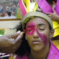 Painting a teenager's face with pink glitter colour.