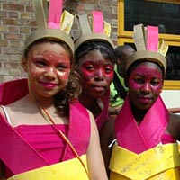 Three girls in pink and yellow, caribean and africa inspired outfits, take a photograph together.