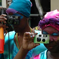 Two members of Elimu, wearing blue and pink outfits, take a photograph.