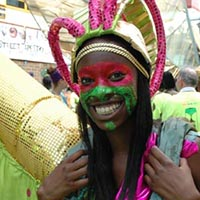 Girl with a red and green face painting, a golden, light green and pink sparkling hat, and a wings-similar costume out of various colours and fabrics.
