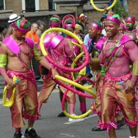 Members of Elimu performing on the street in caribean and african inspired outfits.