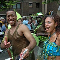 A woman and a man joining the carnival parade. The man is dressed in a dark mesh-shirt and the woman in a blue and green cropped outfit.