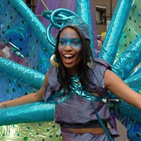 Woman dressed as a peacock-similar creature with a variety of blue and green colours.