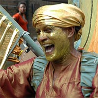 Nolan wearing golden turban with bronze T-shirt and golden wings laughing at the parade