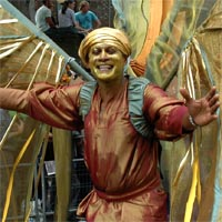 Nolan wearing golden turban, bronze T-shirt and trousers with golden long wings laughing at the parade