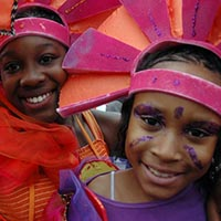 Two children with face-paitings and pink and orange headdresses smiling.