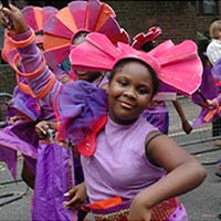 Members of Elimu dressed in purople outfits with orange details and pink headdresses as a part of the carnival parade.
