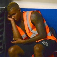 A member of the staff, wearing a orange reflective vest, is sleeping backstage, leaning on a pile of chairs.